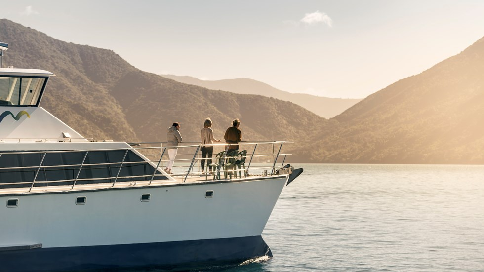 Cruising the Marlborough Sounds at the top of New Zealand's South Island, people view the sun set over the bush clad hills from the bow of MV Odyssea