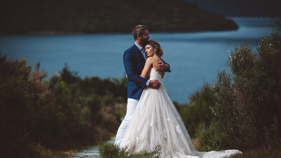 A post-wedding embrace from a bride and groom on the hill above Punga Cove with scenic background views of Endeavour Inlet in the Marlborough Sounds of New Zealand