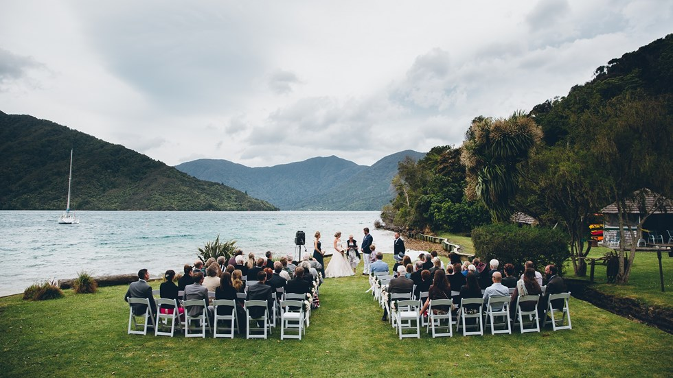 An outdoor wedding ceremony is held on the front lawn at Punga Cove with scenic background views of Endeavour Inlet in New Zealand's South Island Marlborough Sounds