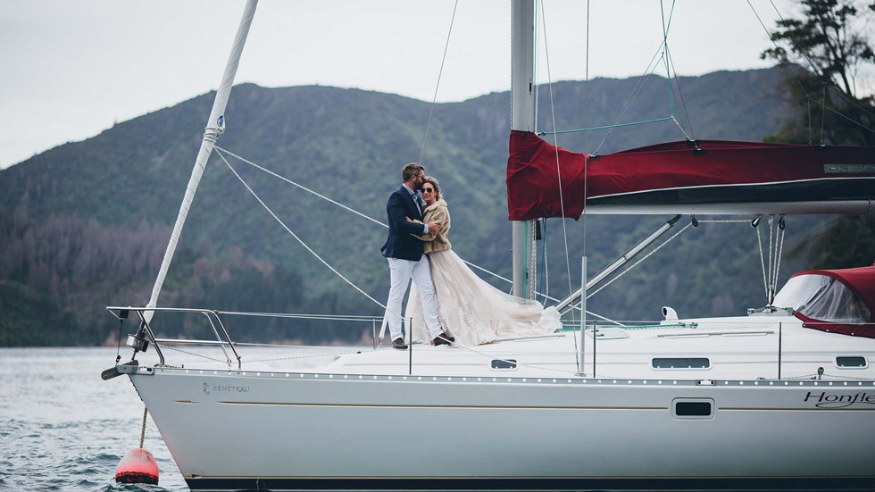 A Bride and Groom embrace on a moored yacht in the Punga Cove bay with Endeavour Inlet scenic views in the Marlborough Sounds of New Zealand