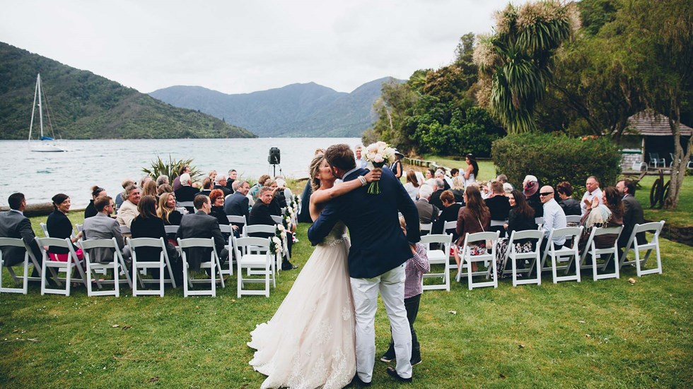 A newly married bride and groom kiss on the front lawn of Punga Cove following the ceremony with watching guests in the Marlborough Sounds of New Zealand