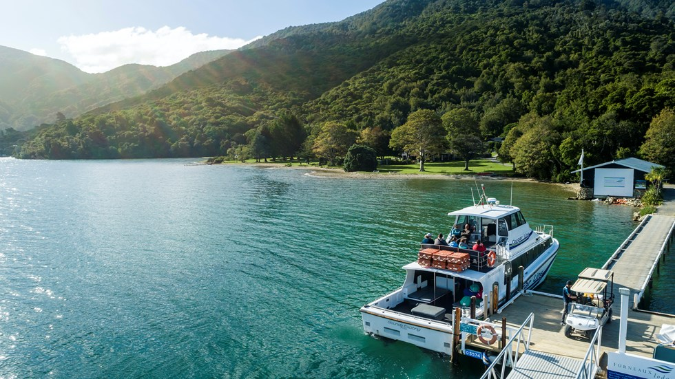 A Cougar Line boat tied up to the jetty at Furneaux Lodge in Endeavour Inlet, Marlborough Sounds, New Zealand.