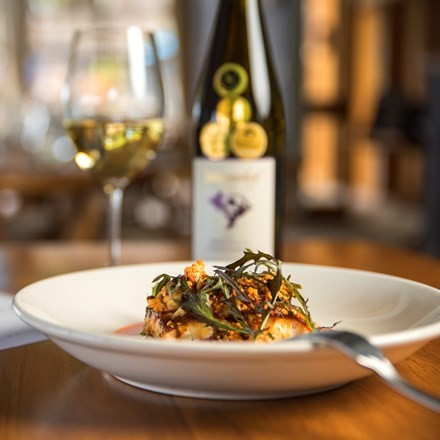 The Punga Fern Restaurant menu can include meals like this fresh Groper dish matched with a glass of local Marlborough wine at Punga Cove in the Marlborough Sounds of New Zealand's South Island