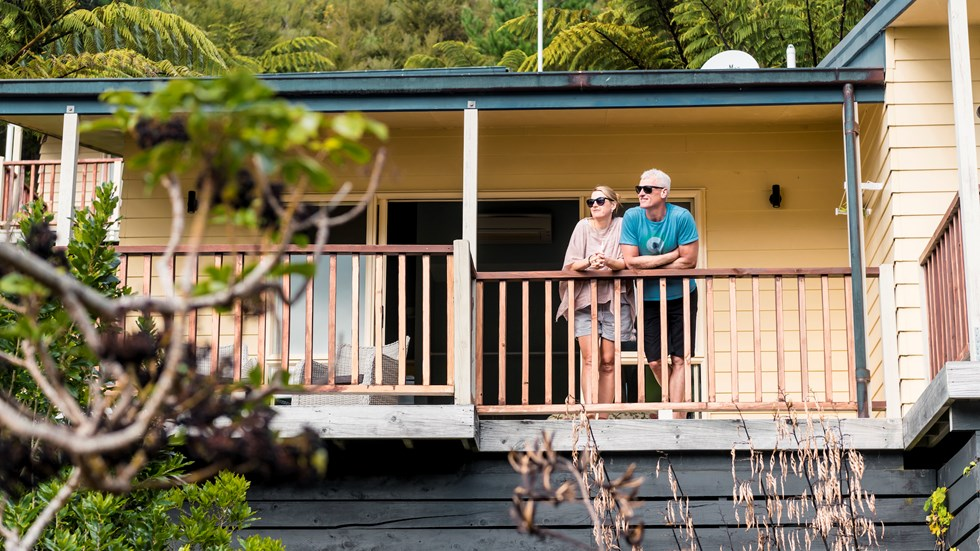 Couple admire scenic Endeavour Inlet views from their Fern Studio balcony at Punga Cove surrounded by Punga ferns in the Marlborough Sounds of New Zealand