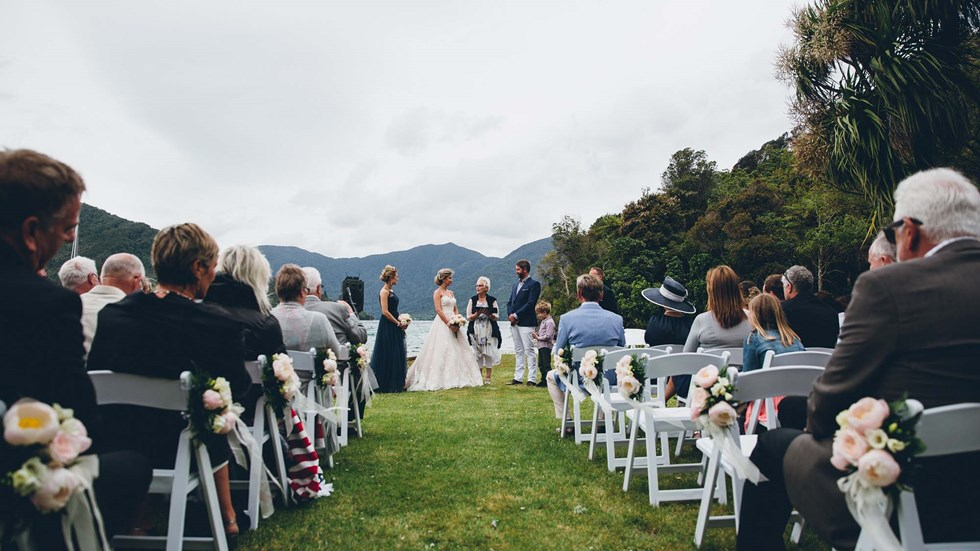 Bride and Groom say their vows at a Punga Cove wedding on the front lawn with seated guests in the Marlborough Sounds of New Zealand