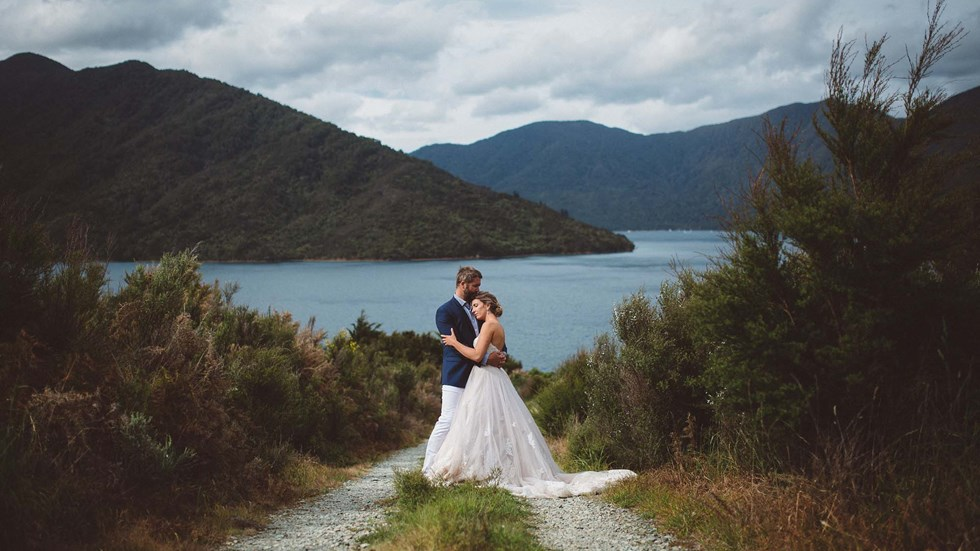 Endeavour Inlet provides a picturesque background for this bride and groom's hug at Punga Cove in New Zealand's South Island Marlborough Sounds