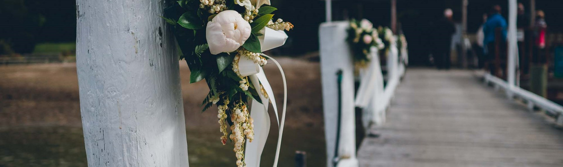 Beautiful floral bouquets are tied to the Punga Cove jetty to welcome guests for a wedding in Endeavour Inlet in the Marlborough Sounds, New Zealand