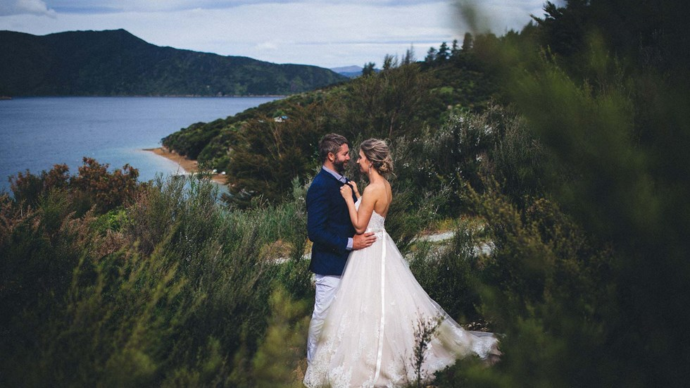 A Bride and Groom face each other on hill above Punga Cove with scenic views of Endeavour Inlet in the background in the Marlborough Sounds of New Zealand