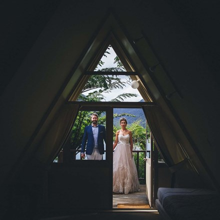 A bride and groom stand holding hands at the entrance of a Koru Chalet room at Punga Cove with a scenic lush Punga fern forest behind them in the Marlborough Sounds, New Zealand