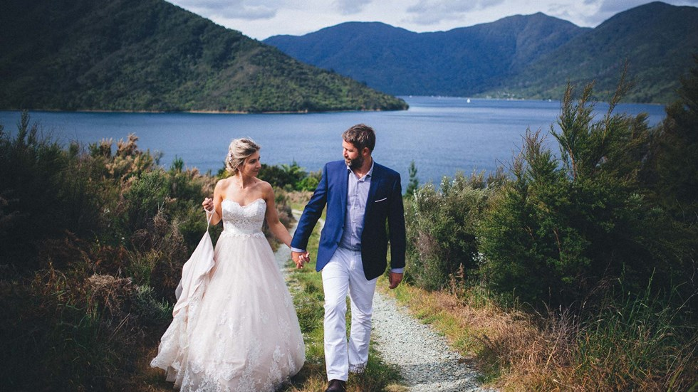 A Bride and Groom walk along a hill above Punga Cove with scenic views of Endeavour Inlet in the background in the Marlborough Sounds of New Zealand