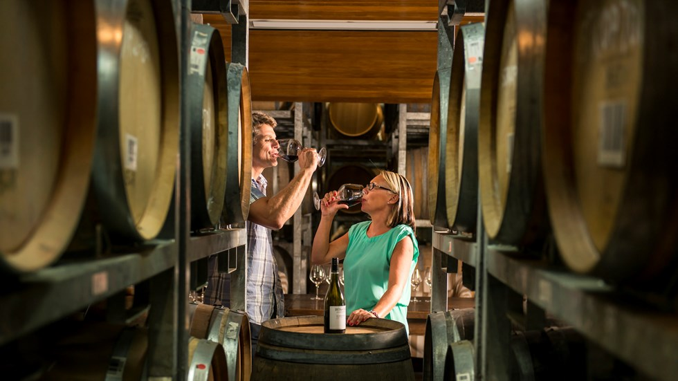 Couple doing a red wine tasting amongst wine barrels in a winery as part of a wine tour in Marlborough, as the top of New Zealand's South Island